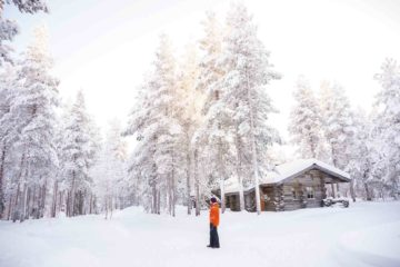 A man looks out at a snowy landscape in Swedish Lapland, Sweden