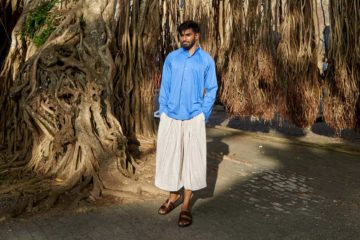 Model wearing white ribbed wide-cut cropped trousers and blue cotton collarless shirt by Homme Plissé Issey Miyake and brown leather 'Chadwick' sandals by Grenson in Galle, Sri Lanka