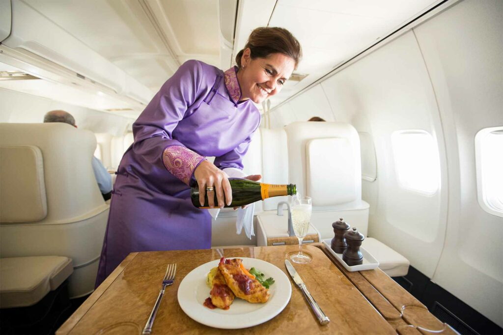 A flight attendant serving lunch and a glass of champagne aboard the Abercrombie & Kent Private Jet