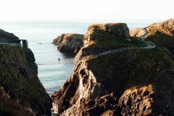 A hiker explores the Carrick-a-Rede Rope Bridge, Northern Ireland